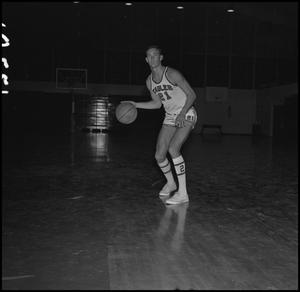 Primary view of object titled '[Doug Reedy dribbling a basketball on the court]'.