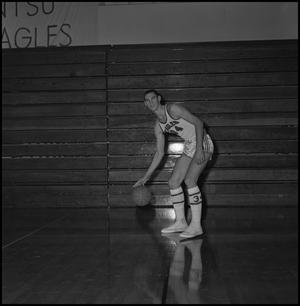 Primary view of object titled '[Carl Miller dribbling basketball]'.