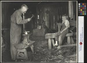 Primary view of object titled '[Unidentified blacksmith working in his shop]'.