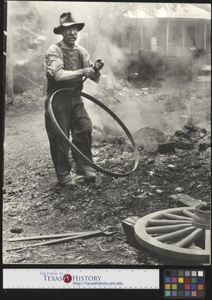 Primary view of object titled '[Alex Cline building a wagon wheel]'.