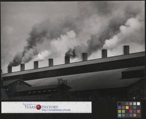 Primary view of object titled '[Smokestacks obscured by building]'.