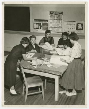 Primary view of object titled '[Six female students working at a table for wise buying]'.