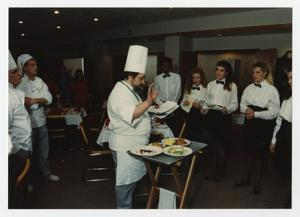 Primary view of object titled '[Chef with documents and tray of food speaks to students]'.
