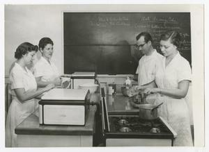 Primary view of object titled '[Four students in classroom cooking]'.