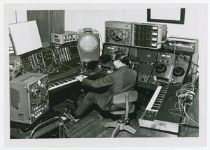 Primary view of object titled '[An unidentified man using the Moog at the NTSU Electronic Music Center Sudio]'.