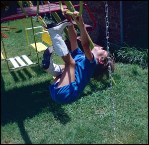 Primary view of object titled '[Child hangs on a swingset]'.