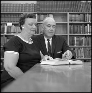 Primary view of object titled '[Dr. and Mrs. Blackburn seated at a library table 2]'.