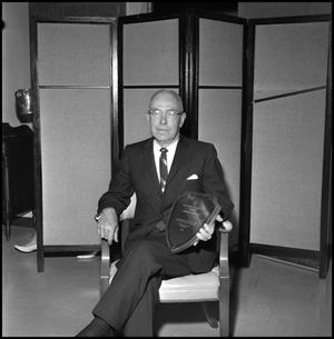 Primary view of object titled '[Dr. Clifford S. Blackburn sitting with award in front of divider]'.