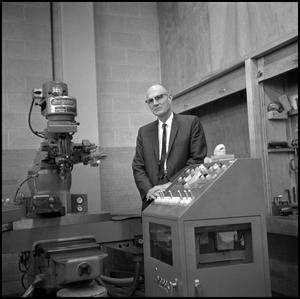 Primary view of object titled '[Dr. Earle Blanton standing behind machine switchboard 1]'.