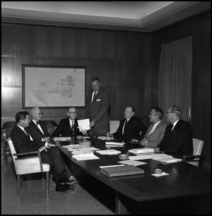 Primary view of object titled '[Board of Regents look at paper during meeting]'.