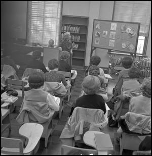 Primary view of object titled '[Teacher standing against podium in class]'.