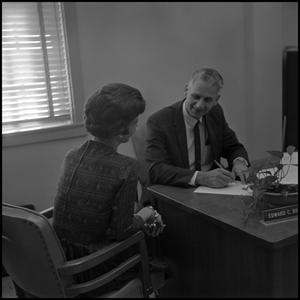 Primary view of object titled '[Dr. Edward Bonk sitting with a woman at his desk]'.