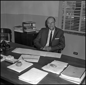 Primary view of object titled '[Dr. Earle Blanton seated at desk, from above 3]'.