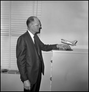 Primary view of object titled '[Dr. Earle Blanton adjusting plane model]'.