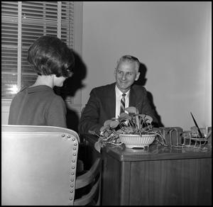 Primary view of object titled '[Dr. Edward Bonk sitting behind his desk in his office]'.