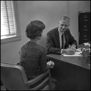 Primary view of object titled '[Dr. Edward Bonk seated at desk in office]'.