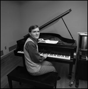 Primary view of object titled '[Bill Blaine sits at piano and looks towards camera]'.