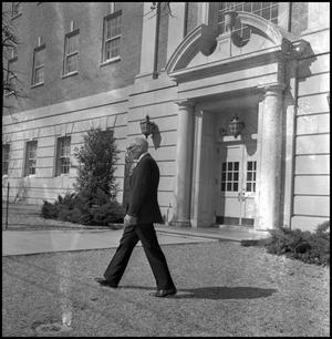Primary view of object titled '[Dean A. Witt Blair walking outside of the Education Home Economics Building]'.