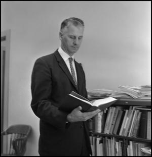 Primary view of object titled '[Dr. Edward Bonk holding a book]'.