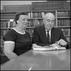 Primary view of object titled '[Dr. and Mrs. Blackburn seated at a library table 1]'.