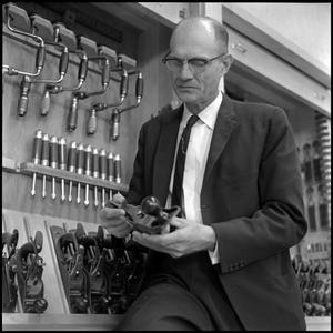 Primary view of object titled '[Dr. Earle Blanton holding tool in workshop]'.