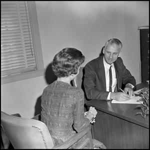 Primary view of object titled '[Dr. Edward Bonk speaking to woman at desk]'.