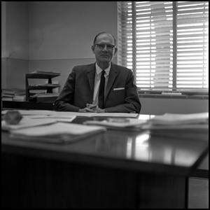 Primary view of object titled '[Dr. Earle Blanton sitting behind desk in office 1]'.