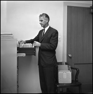 Primary view of object titled '[Dr. Edward Bonk taking a file out of filing cabinet]'.