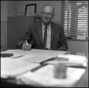 Primary view of object titled '[Dr. Earle Blanton sitting at desk in office 2]'.