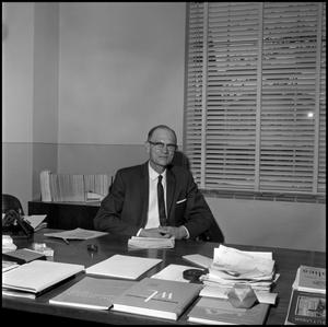 Primary view of object titled '[Dr. Earle Blanton seated at desk, from above 1]'.