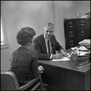 Primary view of object titled '[Dr. Edward Bonk sitting at desk while woman sits next to him]'.