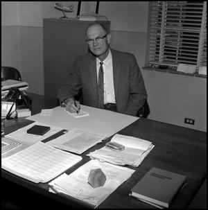 Primary view of object titled '[Dr. Earle Blanton seated behind desk, from above 2]'.