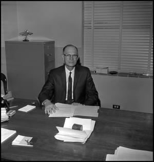Primary view of object titled '[Dr. Earle Blanton seated behind desk, from above 1]'.