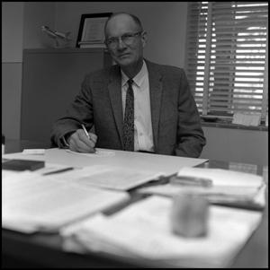 Primary view of object titled '[Dr. Earle Blanton sitting at desk in office 1]'.
