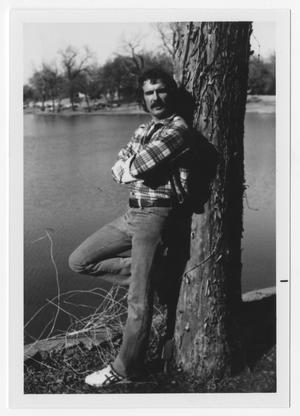 Primary view of object titled '[Bill Nelson leaning against a tree]'.
