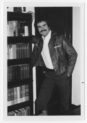Primary view of object titled '[Bill Nelson leaning on bookcase]'.