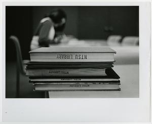 Primary view of object titled '[NTSU Willis Library interior picture of books and student studying]'.