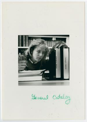 Primary view of object titled '[Student viewing NTSU Library books]'.