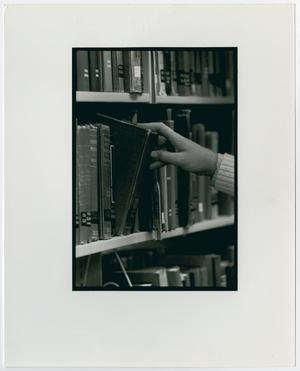Primary view of object titled '[Student pulling a book from the shelf in the Willis Library]'.