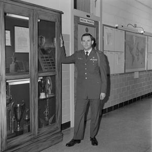 Primary view of object titled '[John Spencer Church in uniform standing beside a trophy case]'.