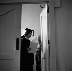 Primary view of object titled '[Graduate receiving commencement ceremony information]'.