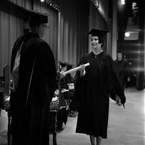Primary view of object titled '[Faculty handing diploma to student on stage]'.