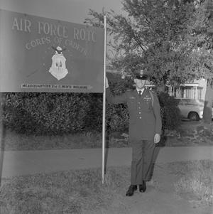 Primary view of object titled '[John Spencer Church in uniform standing beside an Air Force R.O.T.C. sign]'.
