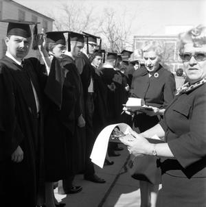 Primary view of object titled '[Graduates lined up outside for commencement 1962]'.