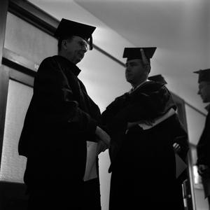 Primary view of object titled '[Faculty talking in hallway at commencement 1961]'.