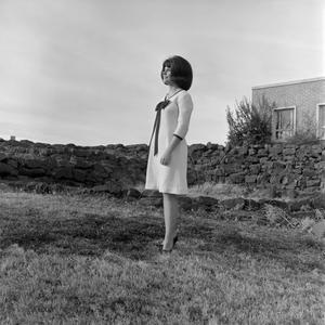 Primary view of object titled '[Patsy Gray Cloud standing in front of a rock wall]'.