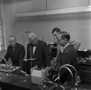 Primary view of object titled '[Four males conducting research in the Chemistry lab]'.