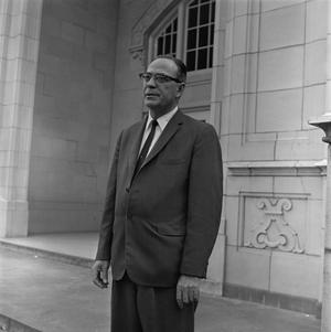 Primary view of object titled '[Dr. Ernest Clifton standing in front of the Auditorium English Building]'.