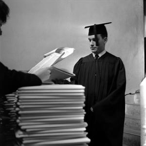 Primary view of object titled '[Graduate looking at commencement ceremony information]'.
