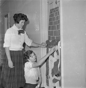 Primary view of object titled '[Girls decorating door in Terrill Hall]'.